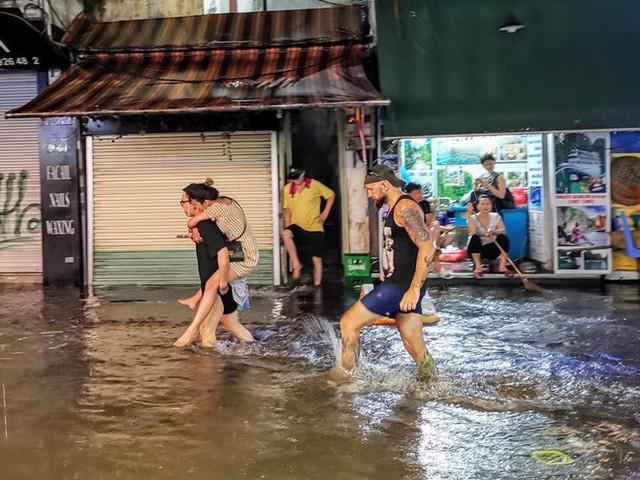 Hà Nội mưa lớn dịp nghỉ lễ 30/4-1/5, nhiều tuyến phố biến thành sông, khách Tây lội bì bõm - Ảnh 4.