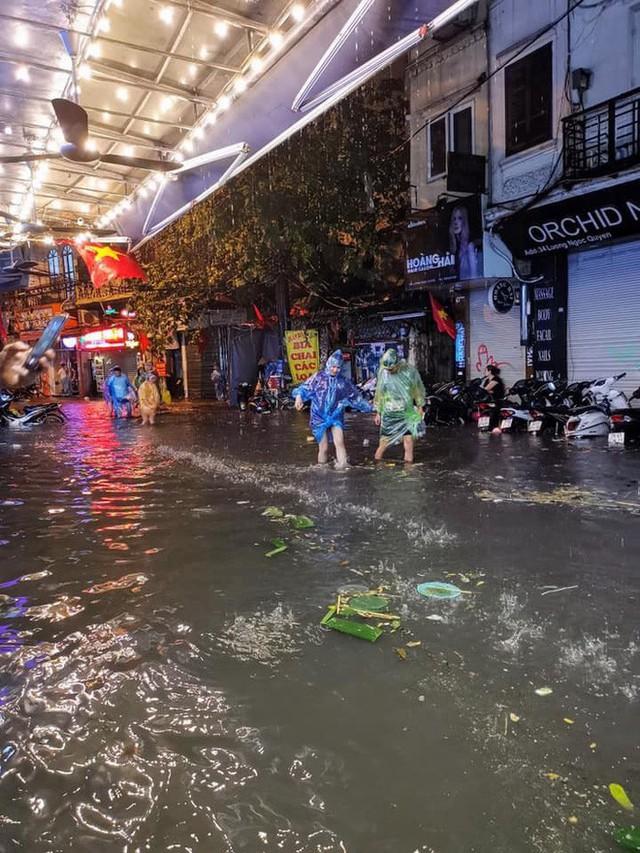 Hà Nội mưa lớn dịp nghỉ lễ 30/4-1/5, nhiều tuyến phố biến thành sông, khách Tây lội bì bõm - Ảnh 10.