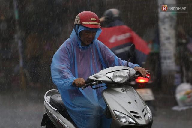 Mưa lớn bất ngờ đổ xuống Sài Gòn, nhiều người phải bật đèn xe lưu thông - Ảnh 1.