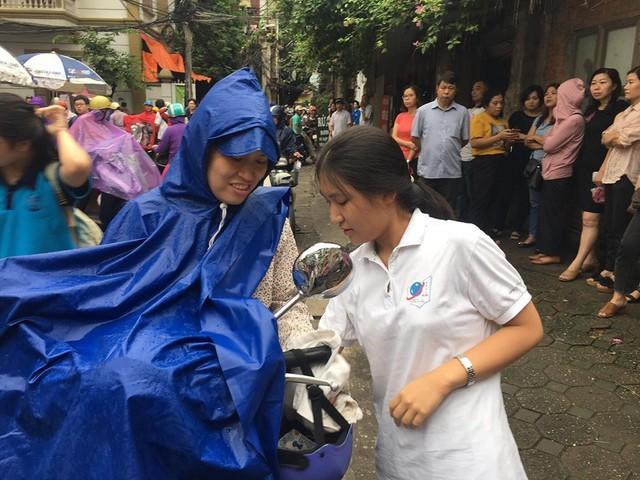 Thi vào lớp 10 ở Hà Nội: Phụ huynh đội mưa đưa con đi thi từ mờ sáng - Ảnh 1.