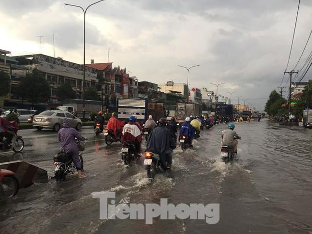 Nước chảy như thác đổ sau mưa, nhiều tuyến đường ở Sài Gòn ngập nặng - Ảnh 1.