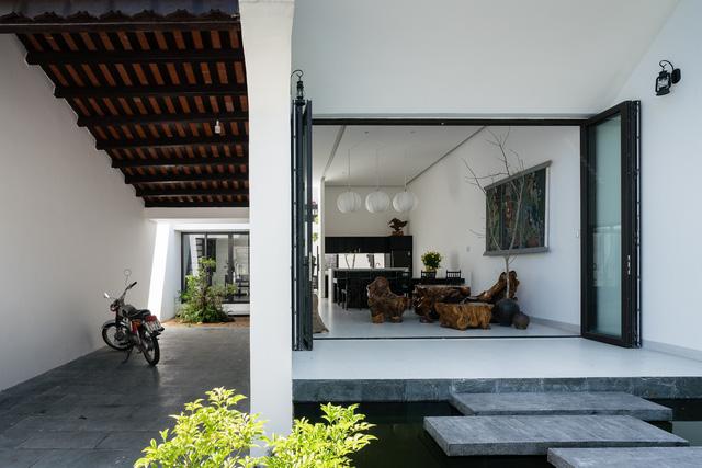 Sau cánh cổng, ngôi nhà như được chia làm 2 phần rõ rệt, một bên là phòng khách, bên còn lại là hành lang, đồng thời là chỗ để xe.