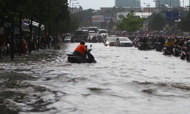 CLIP: Nước cuồn cuộn cuốn ngã xe máy trong cơn mưa lớn ở TP HCM  - Ảnh 2.