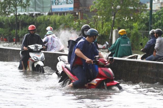 CLIP: Nước cuồn cuộn cuốn ngã xe máy trong cơn mưa lớn ở TP HCM  - Ảnh 3.
