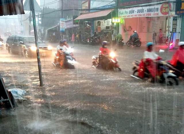 CLIP: Nước cuồn cuộn cuốn ngã xe máy trong cơn mưa lớn ở TP HCM  - Ảnh 5.