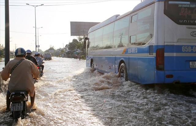 Quốc lộ 1A chìm trong nước, CSGT huy động xe chuyên dụng giải cứu - Ảnh 1.