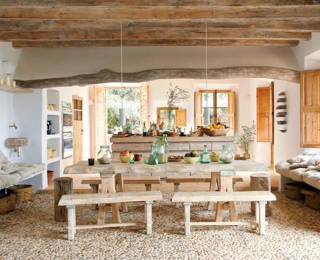 Căn phòng được thiết kế mang phong cách dân dã. Nổi bật là sàn nhà làm bằng đá và sỏi, xung quanh bàn ăn có 4 chiếc ghế dài được đóng đơn giản.