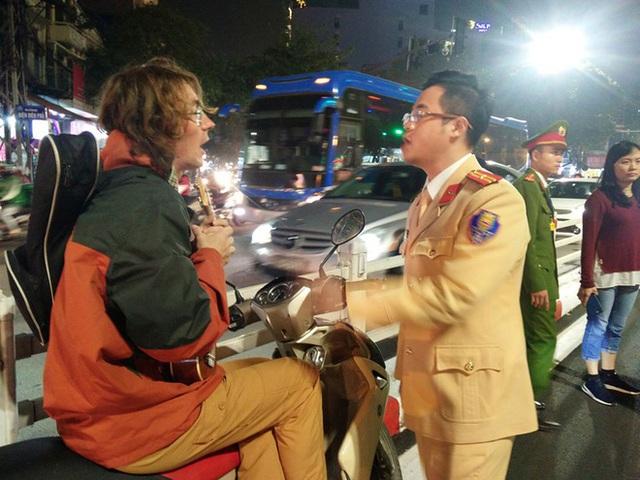 Bị CSGT dừng xe vì không đội mũ bảo hiểm, thanh niên người nước ngoài mang đàn ra ngồi hát - Ảnh 1.