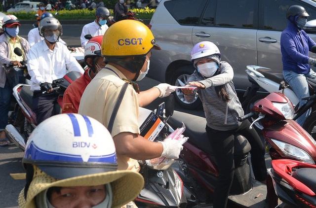 Giữa trưa, CSGT phát khẩu trang y tế cho người dân ở cửa ngõ Tân Sơn Nhất  - Ảnh 3.