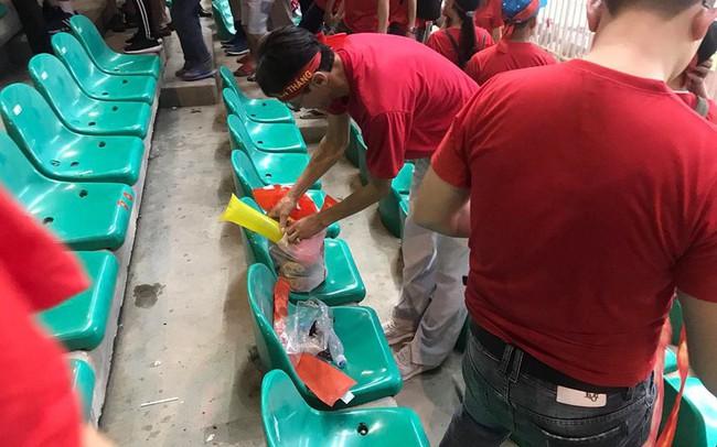 Cổ động viên Việt Nam nán lại thu dọn rác trên khán đài sau trận bán kết ASIAD 2018 ở Indonesia