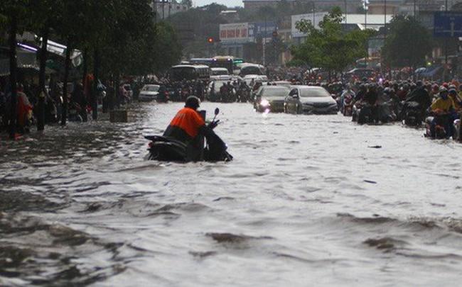 CLIP: Nước cuồn cuộn cuốn ngã xe máy trong cơn mưa lớn ở TP HCM