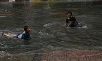 Trẻ em bơi giữa đường phố Sài Gòn sau cơn mưa lớn