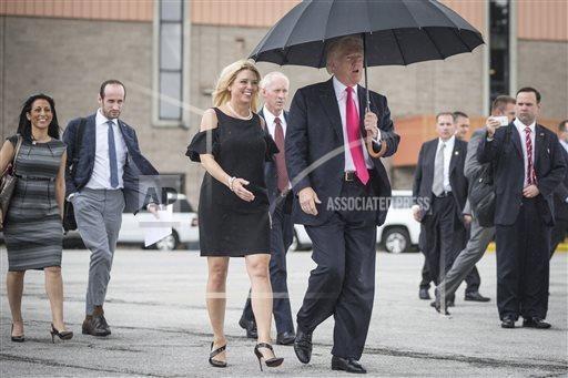 Ông Trump che ô để bảo vệ mái tóc của mình. (Nguồn: AP)