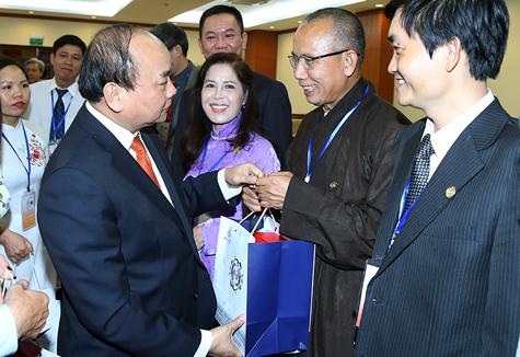 Thủ tướng trao quà tặng đại biểu kiều bào. Ảnh: VGP/Quang Hiếu