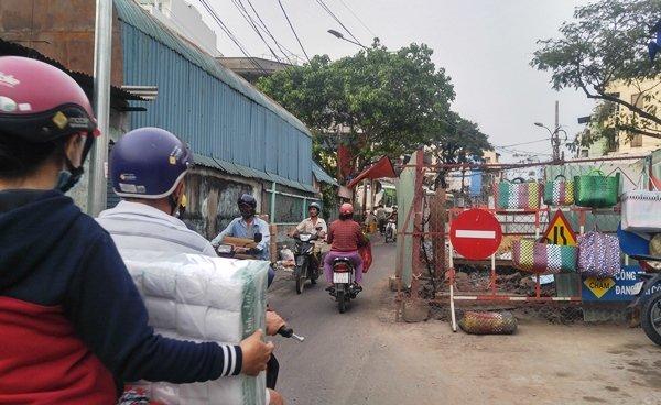 """Tương tự, khu vực phía trước chợ Kim Biên (Q.5), công trình thi công kênh Hàng Bàng đang trong quá trình hoàn thiện. """"Lô cốt"""" kéo dài trên nhiều tuyến đường, có nhiều chỗ phần ống cống và vật liệu để ngổn ngang bừa bộn, tràn ra mặt đường."""