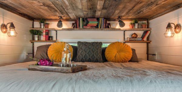 Góc nghỉ ngơi cũng được chau chút và nhấn nhá bởi những chiếc gối màu vàng bắt mắt. Bên trên là hệ thống kệ làm nơi để sách và những đồ dùng trang trí.