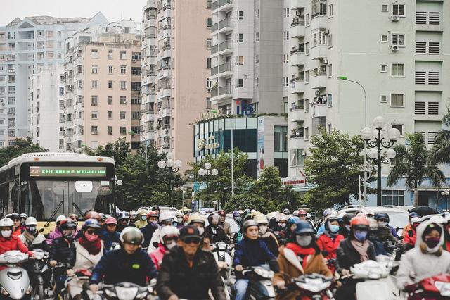 Xe buýt lưu thông trên tuyến đường này buộc phải len lỏi giữa dòng xe máy ùn ùn vây quanh.