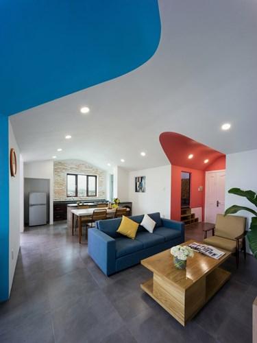 Phòng khách và bếp ăn được bố trí mở khiến không gian càng trở nên thoáng rộng. Chiếc sofa màu xanh đặt quay lưng lại với khu bếp có chức năng là bức tường ngăn cách giữa hai khu vực.