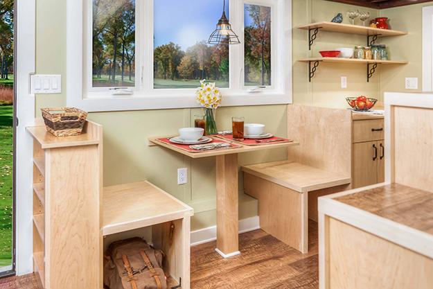 Ngay cạnh lối vào nhà là chiếc bàn gỗ nhỏ kế hợp vơi những chiếc ghế tích hợp tủ đựng đồ. Chiếc bàn nhỏ cạnh cửa sổ thoáng mát này vừa có thể làm không gian tiếp khách, là nơi làm việc và khi không dùng đến nó lại trở thành bàn ăn lý tưởng cho chủ nhà.