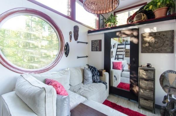 Phòng khách sang trọng với bộ sofa trắng muốt cùng chiếc cửa sổ kính hình elip ấn tượng. Bên trên là hai gác xép nhỏ làm nơi nghỉ ngơi và góc thư giãn của chủ nhà.
