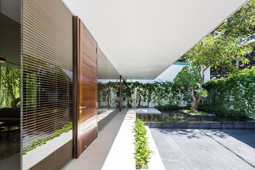 Toàn bộ phần mặt tiền thay vì xây tường chủ nhà chọn cửa gỗ gấp và mành che khiến tầm nhìn từ phòng khách và bếp không bị hạn chế.