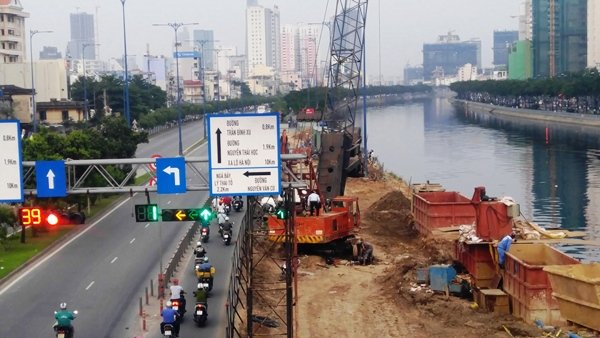 Tại chân cầu Nguyễn Văn Cừ (Q.1), công trình xây dựng cầu nối đường Võ Văn Kiệt với cầu Nguyễn Văn Cừ đang được rào chắn, lấn chiếm mặt đường.
