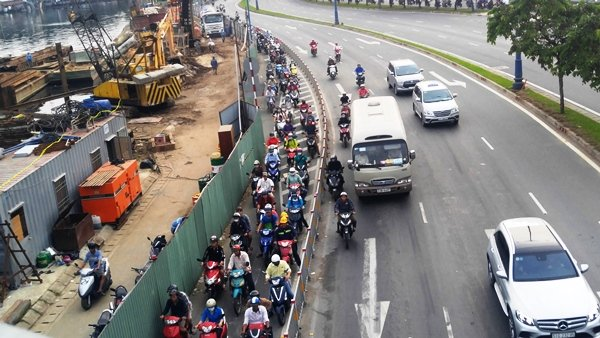 Một đoạn đường dài hơn 500m bị chiếm dụng để, lắp đặt rào chắn khiến giao thông qua khu vực bị ùn ứ. Nhiều xe máy chạy len lỏi ra giữa làn đường ô tô, rất nguy hiểm.
