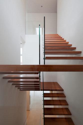 Những bậc cầu thang gỗ màu kết hợp với bức tường trắng sáng tạo cảm giác hài hòa, thoải mái khi đi lại.