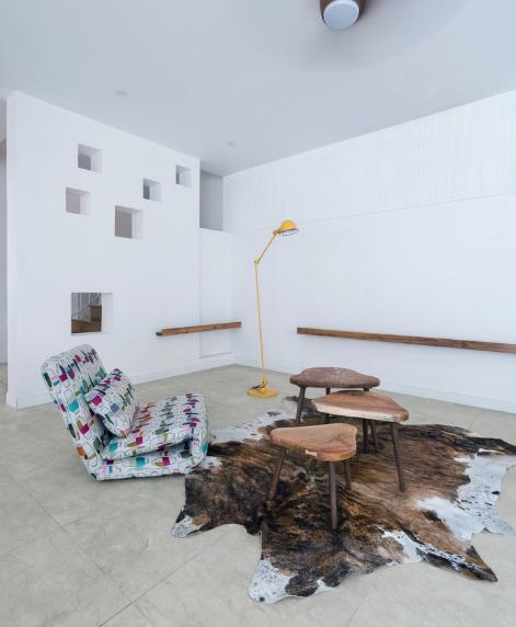 Phòng khách được thiết kế đơn giản với chiếc ghế lười và những bàn trà nhỏ.
