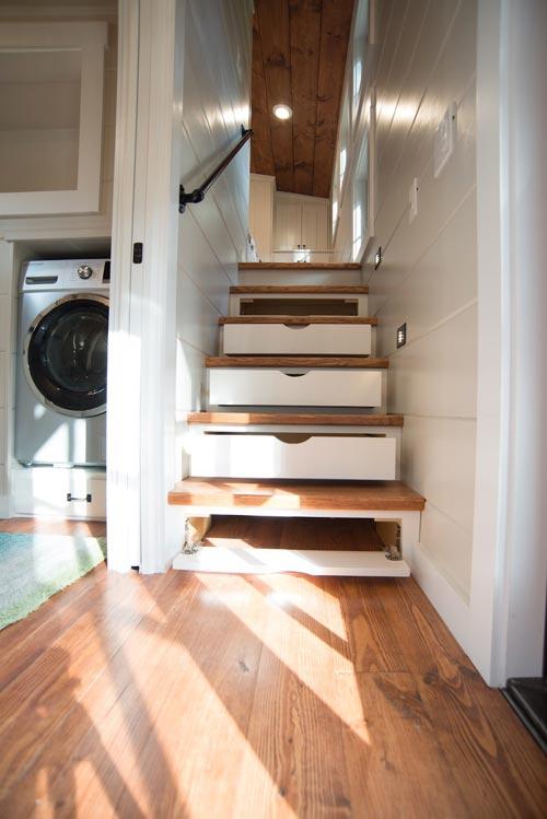 Một cầu thang gỗ dẫn lên gác xép với mỗi bậ là một ngăn kéo trữ đồ thuận tiện.