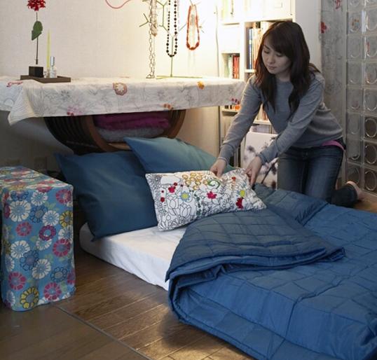 """Ẩn nấp bên dưới chiếc bàn được trải khăn hoa xinh xắn này là khu vực lưu trữ những món đồ cần thiết cho một chiếc """"giường ngủ di động"""" vô cùng tiện lợi."""