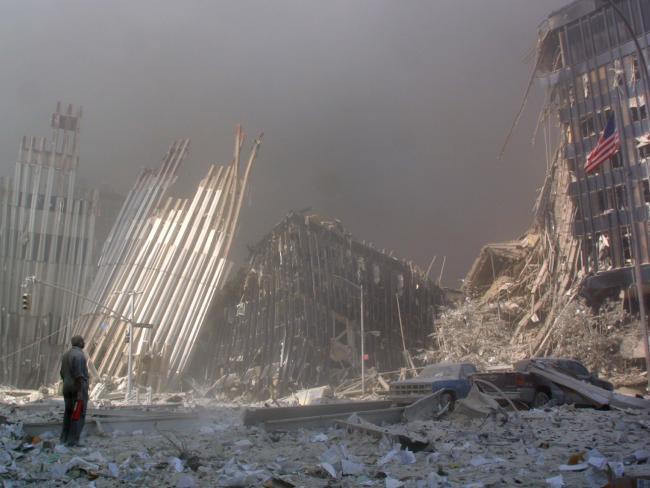 Một người đàn ông đứng trước đống đổ nát và cố gắng tìm kiếm những người còn sống sót đang cần sự giúp đỡ.