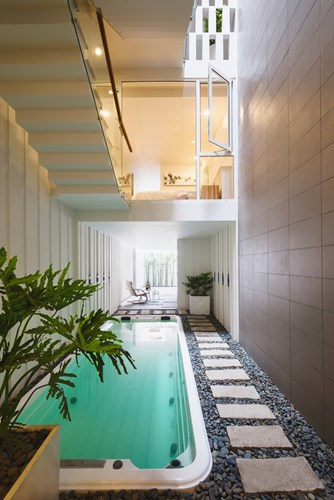 Tầng 1 được bố trí bể bơi và cây xanh khiến không gian ngôi nhà trở nên dịu mát.