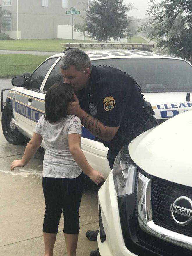 Bức ảnh hai bố con cảnh sát Seth Stiers tạm biệt nhau trong mưa bão đã khiến nhiều người cảm động. (Ảnh: Facebook)