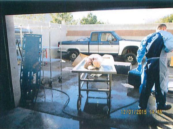 Người đàn ông trong trang phục bảo hộ y tế đang cầm vòi xịt nước nhằm mục đích rã đông xác chết.