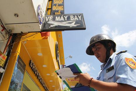Lực lượng đô thị lập biên bản đối với cửa hàng bán vé máy bay lắp bản quảng cáo dư ra phần vỉa hè.
