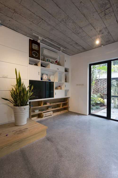 Sự đơn giản, dân dã của ngôi nhà thể hiện rất rõ qua việc sử dụng nội thất: sàn láng xi măng, trần bê tông, và bức tường gạch mộc.
