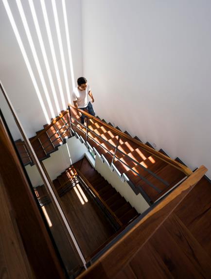 Cầu thang gỗ ngập nắng là lối duy nhất dẫn lên tầng 2 và 3 của ngôi nhà.