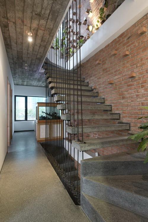 Bức tường gạch mộc xuyên suốt cầu thang từ tầng 1 lên tầng 4 tạo điểm nhấn bắt mắt cho ngôi nhà.