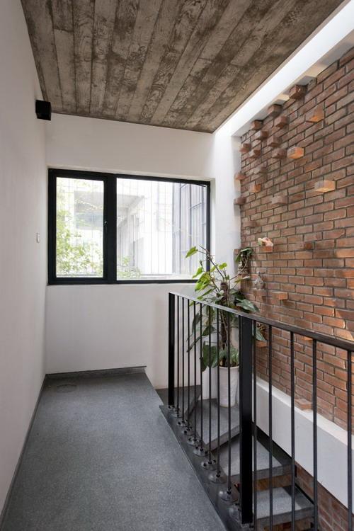 Không gian cầu thang cũng được thiết kế đơn giản với lan can bằng những thanh thép thẳng đứng.