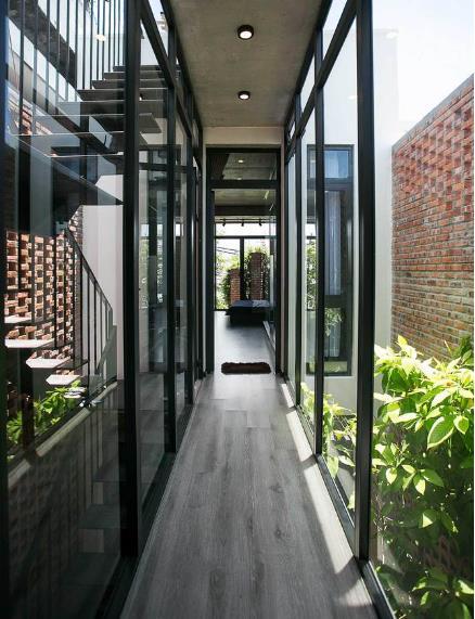 Hai hành lang dài với cây xanh và gió trời ở hai bên được nối với phòng ngủ.
