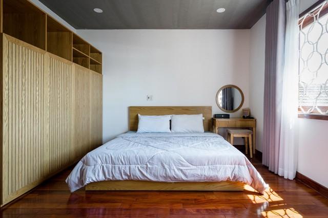 Phòng ngủ thoáng sáng và vô cùng tiện nghi với hệ thống tủ kệ gỗ trữ đồ ngay cạnh chiếc giường. Toàn bộ sàn nhà được lát gỗ sáng màu.