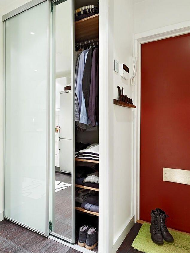Lối vào nhà nổi bật với cánh cửa sơn đỏ, bên cạnh là tủ để quần áo, dày dép kết hợp với giương soi vừa thuận tiện mỗi khi chủ nhà sửa soạn ra ngoài, vừa có tác dụng nhân đôi diện tích nơi góc nhỏ này.