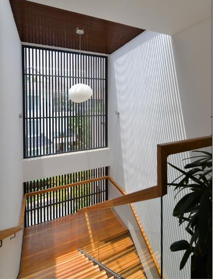 Thay vì bức tường bí bách, hệ gỗ lam vừa giúp lối đi lên các tầng thoáng sáng, vừa mang tính thẩm mỹ cho ngôi nhà.
