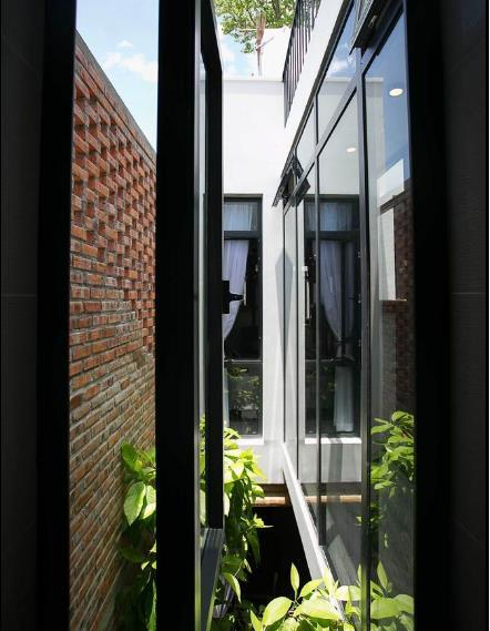 Cửa sổ kính mở ra khu giếng trời với nhiều cây xanh. Nhờ thiết kế thông minh này mà nằm trong phòng ngủ chủ nhà cũng có thể cảm nhận được từng sự biến đổi của thời tiết bên ngoài.