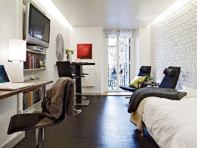 Điều đáng chú ý trong thiết kế nội thất của căn hộ nhỏ này đó là chủ nhà sử dụng bức tường gạch thô chạy dọc suốt chiều dài khu vực phòng khách mang đến không khí ấm áp, bình dị nhưng vẫn hiện đại và lôi cuốn cho không gian.