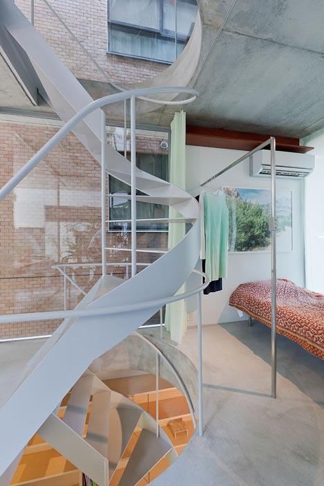 Chiếc cầu thang xoắn ốc tiết kiệm không gian được thiết kế khéo léo đi qua các lỗ tròn xuyên qua lớp sàn bê tông dày.