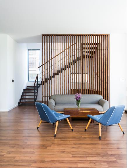 Sàn nhà được ốp gỗ cùng với hệ lam nơi phòng khách tạo cảm giác ấm cúng và thân thiện cho khách vào nhà.