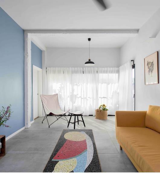 Chiếc thảm trải sàn nhiều màu lạ mắt cộng bức tường sơn xanh cũng là các điểm nhân bắt mắt cho bất kỳ ai bước chân vào nhà.