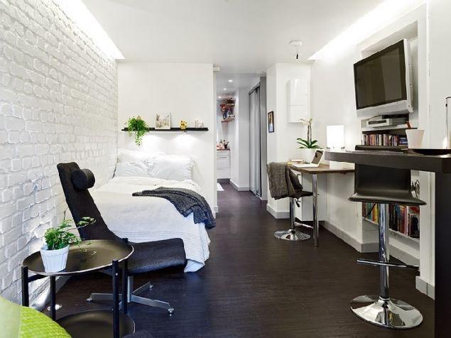 Phía cuối ngôi nhà là khu vực tiếp khách và bàn ăn với nội thất được sử dụng nhỏ gọn và tiện dụng. Tận dụng góc khuyết của căn phòng chủ nhà dùng làm góc treo tivi và những kệ sách xinh xắn vừa vặn với không gian nhỏ.